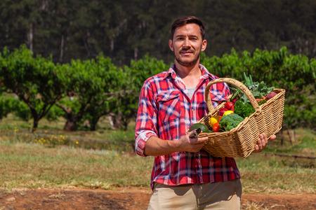 Organic farmer with fresh fruit and vegetables in garden Standard-Bild