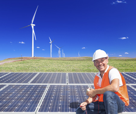 energy fields: Sustainable clean energy technician with solar panels and wind turbines Stock Photo