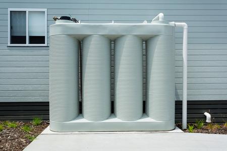 Regenwasser-Sammeltank neben einem modernen Haus Standard-Bild - 35368799