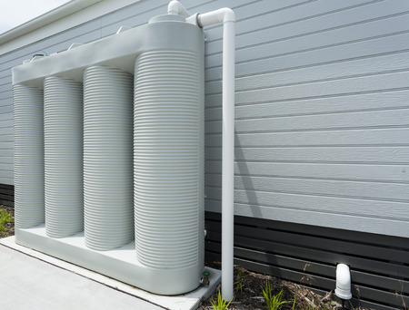 Rainwater collection tank besides a modern house Stock Photo