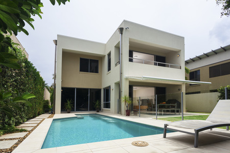 Modern tropical villa exterior with sunny pool 스톡 콘텐츠