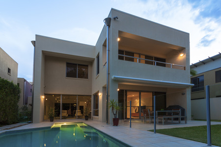 Modern home exterior with pool at dusk Stock fotó