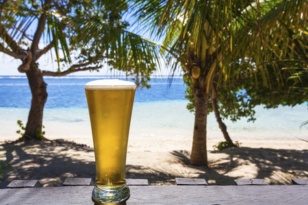 samoa: Cold beer on tropical beach with coconut palms Stock Photo