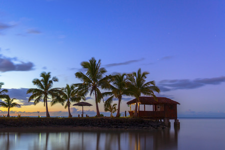 fale: Palm trees and beach hut at sunset on Samoa Stock Photo
