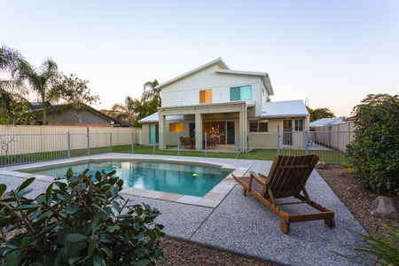glass fence: Modern home exterior with pool at dusk Stock Photo