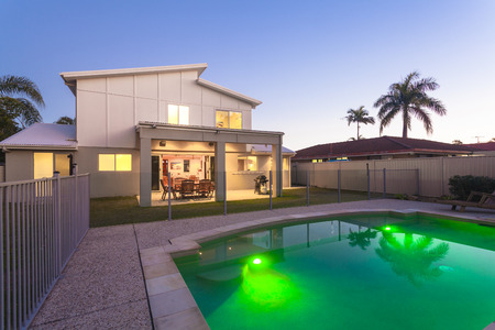 Modern home exterior with pool at dusk Banque d'images