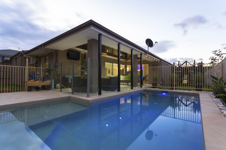 Swimming pool and outdoor entertaining area in stylish home at dusk Stock fotó