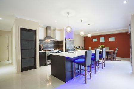 case moderne: Cucina illuminata a LED e tavolo da pranzo in casa moderna alla moda