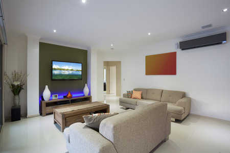 Stylish living area with flat screen TV and air conditioning