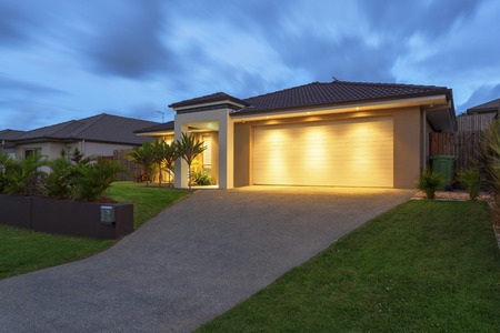 Well lit modern home exterior at dusk Stock Photo