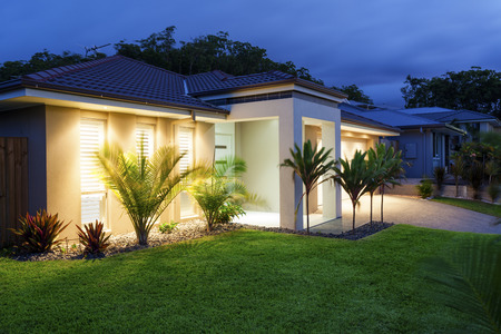 house facades: Well lit modern home exterior at dusk Stock Photo