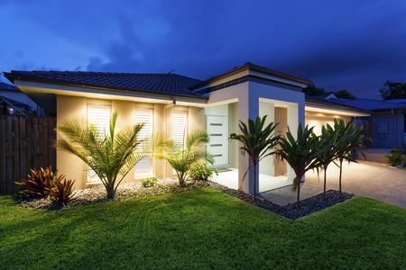 Well lit modern home exterior at dusk Banque d'images