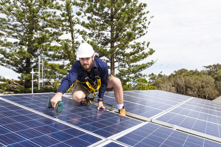Solar panel technician with drill installing solar panels on roof Banque d'images