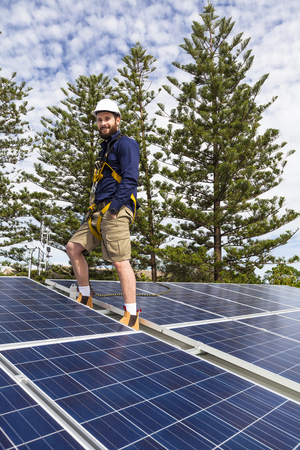 installer: Solar panel technician with safety equipment on roof Stock Photo