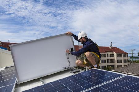 지붕에 태양 전지판 설치를 검사하는 솔라 패널 기술자 스톡 콘텐츠