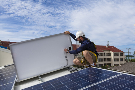 Solar panel technician checking solar panel installation on roof