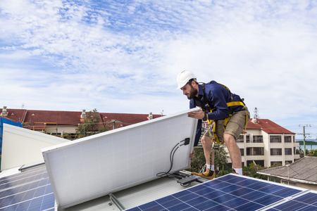 solar equipment: Solar panel technician checking solar panel installation on roof