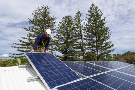 installation: Solar panel technician installing solar panels on roof Stock Photo
