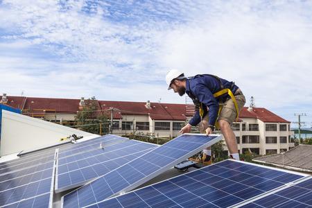 Solar panel technician installing solar panels on roof Foto de archivo
