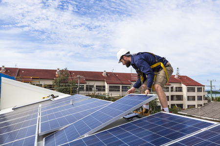 solar equipment: Solar panel technician installing solar panels on roof Stock Photo