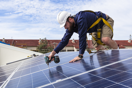 install: Solar panel technician with drill installing solar panels on roof Stock Photo