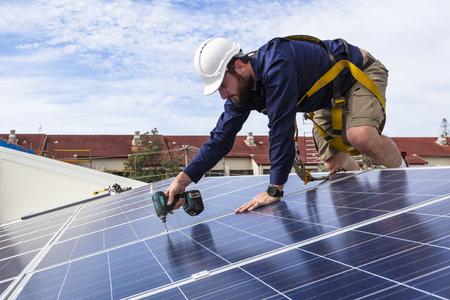 Technicien de panneau solaire avec une perceuse installation de panneaux solaires sur le toit Banque d'images - 49589598