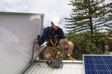Solar panel technician measuring solar output on roof