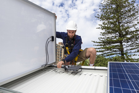 human energy: Solar panel technician measuring solar output on roof