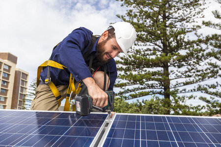 installations: Solar panel technician with drill installing solar panels on roof Stock Photo