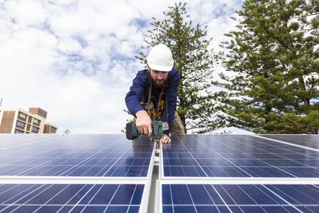 Solar panel technician with drill installing solar panels on roof Foto de archivo