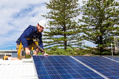 太陽電池パネルを持つ技術者がドリルの屋根にソーラー パネルを設置