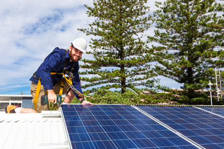 installation: Solar panel technician with drill installing solar panels on roof Stock Photo