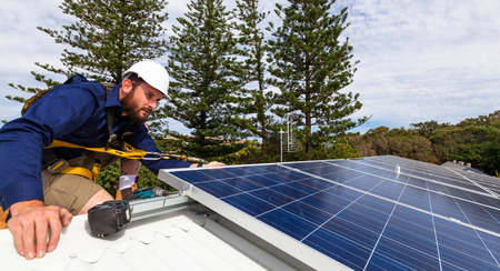solar equipment: Solar panel technician with drill installing solar panels on roof Stock Photo