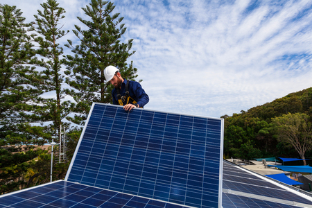 install: Solar panel technician installing solar panels on roof Stock Photo