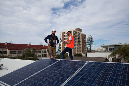 installer: Solar panel technician and client with laptop house roof