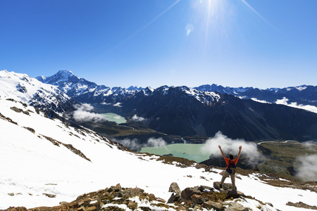 Hiker on top of mountain looking at Mount Cook Reklamní fotografie
