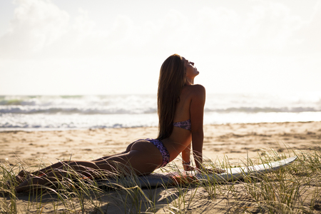 sand surfing: Sexy young woman with surfboard on beach at sunrise.