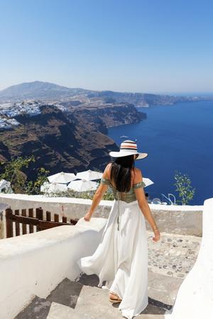santorini: Attractive woman walking in sunny Santorini, Greece Stock Photo