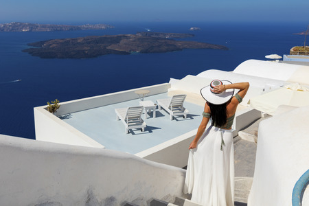 island: Stylish attractive woman standing in sunny Santorini, Greece