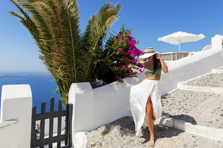 europe: Attractive woman walking in sunny Santorini, Greece Stock Photo