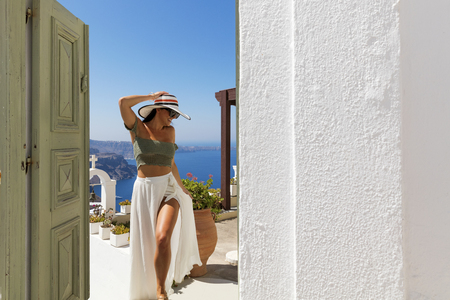 island: Attractive woman walking in sunny Santorini, Greece Stock Photo
