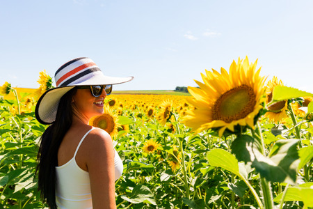 Happy attractive woman in sunflower field on a sunny day Stock Photo