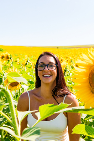 Laughing attractive woman in sunflower field on a sunny day