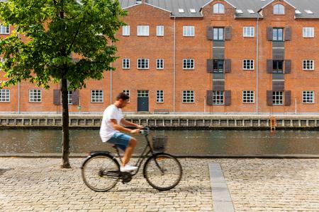 Cyclist on Copenhagen bike lane near canal