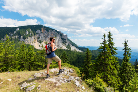 Male hiker on mountain top on a summer day
