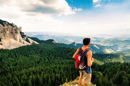 Männlicher Wanderer auf Bergspitze an einem Sommertag Lizenzfreie Bilder