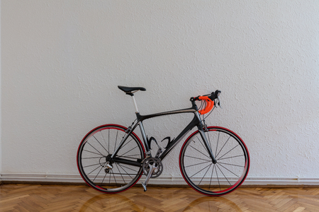 Race bike next to white wall on wooden floor