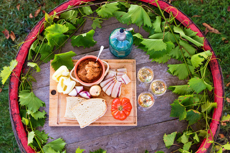 Rustic outdoor picnic setting at winery with wine and food