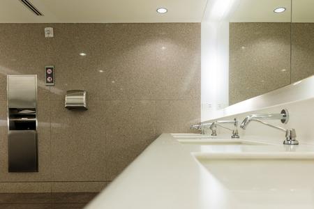 Öffentliche Badezimmerausstattung mit Waschbecken, Wasserhähnen und Händetrockner