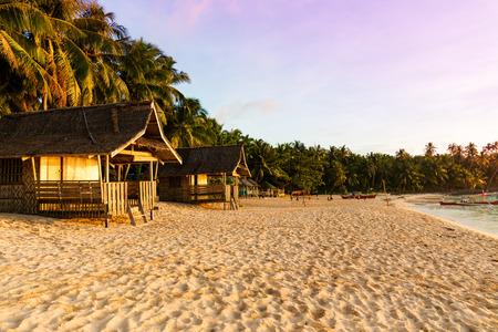 Beach hut on pristine tropical Philippine island at sunset Standard-Bild